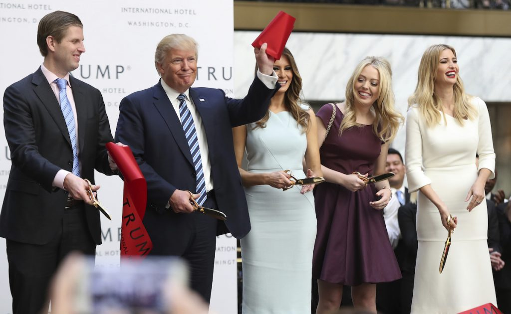 Donald Trump, together with his family, from left, Eric Trump, Melania Trump, Tiffany Trump and Ivanka Trump, waves part of a ribbon after cutting the ribbon during the grand opening of Trump International Hotel in Washington, Wednesday, Oct. 26, 2016. AP Photo/Manuel Balce Ceneta