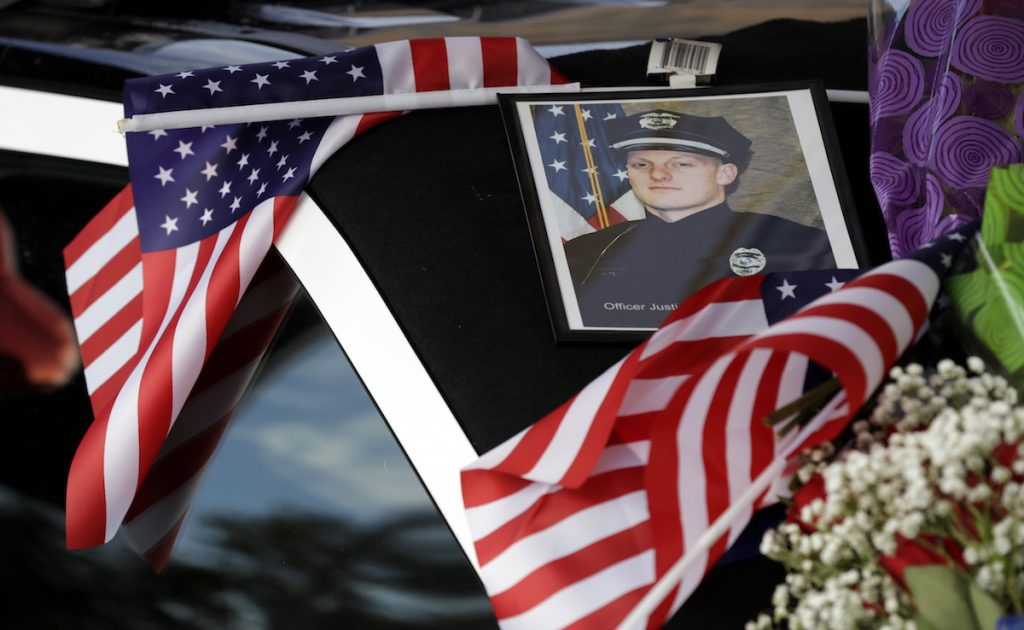 A photo of Urbandale officer Justin Martin is seen on a memorial outside the Urbandale Police Department, Wednesday, Nov. 2, 2016, in Urbandale, Iowa. Martin and Des Moines officer Sgt. Anthony Beminio were ambushed and fatally shot in separate attacks Wednesday. AP Photo/Charlie Neibergall