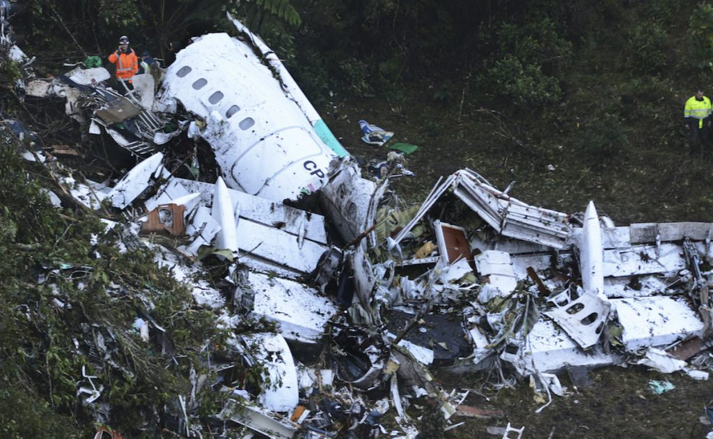 Rescue workers stand at the wreckage site of a chartered airplane that crashed in a mountainous area outside Medellin, Colombia, Tuesday, Nov. 29, 2016. AP Photo/Luis Benavides