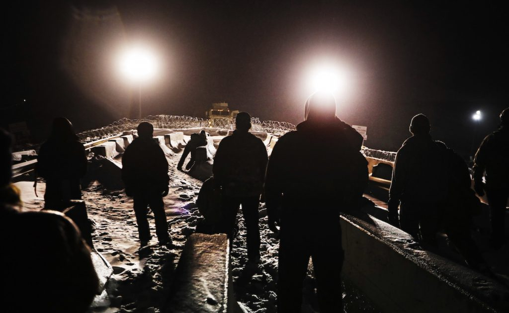 Military veterans walk onto a closed bridge to protest across from police protecting the Dakota Access oil pipeline site in Cannon Ball, N.D. December 1, 2016. AP Photo/David Goldman